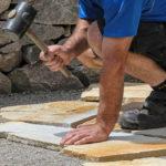 Obrero colocando piedras con un mazo de goma.